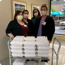 A group of masked healthcare workers with a cart of boxed lunches