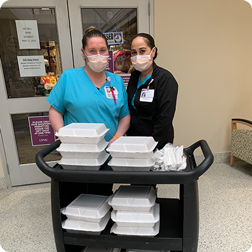 Two masked healthcare workers with a cart of boxed lunches