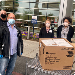 Masked restaurant and healthcare workers exchanging boxes of food