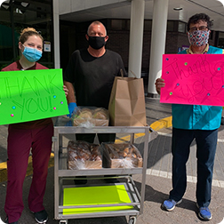 Three masked people with thank you signs posing with a cart of bagels and muffins from Cafe Fresco