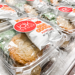 A close up of boxed lunches from JDK Group each containing wraps, a bag of chips, and a cookie.